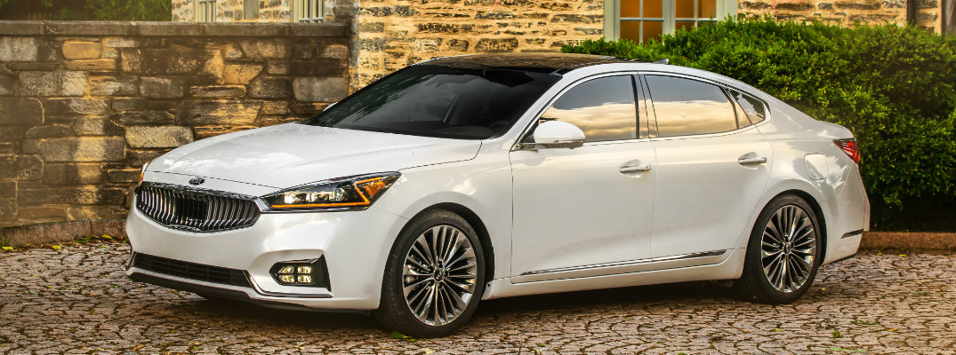 2019 Kia Cadenza exterior shot with white paint color parked on a stone tiled plaza outside a old fashioned luxury country house
