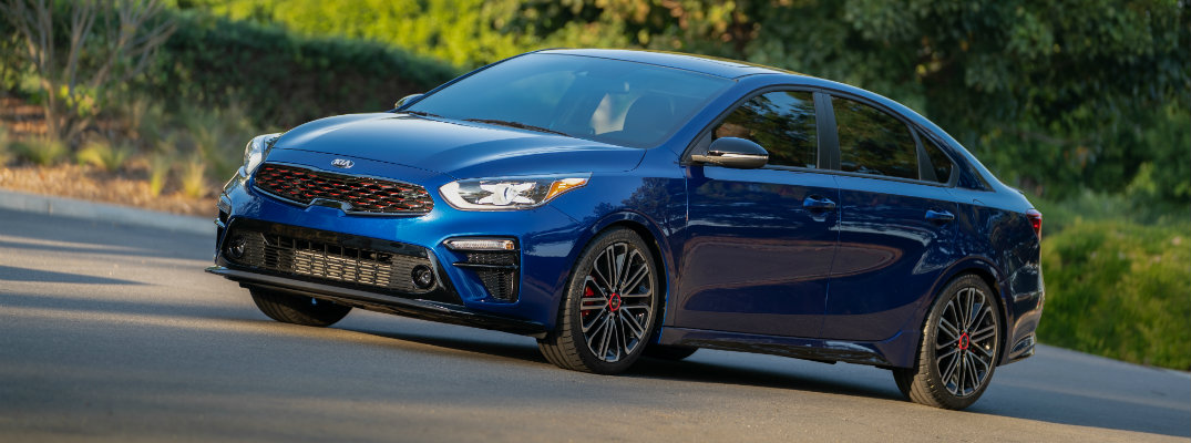 2020 Kia Forte GT trim level exterior shot with blue paint color parked on a lot with green bushes behind it