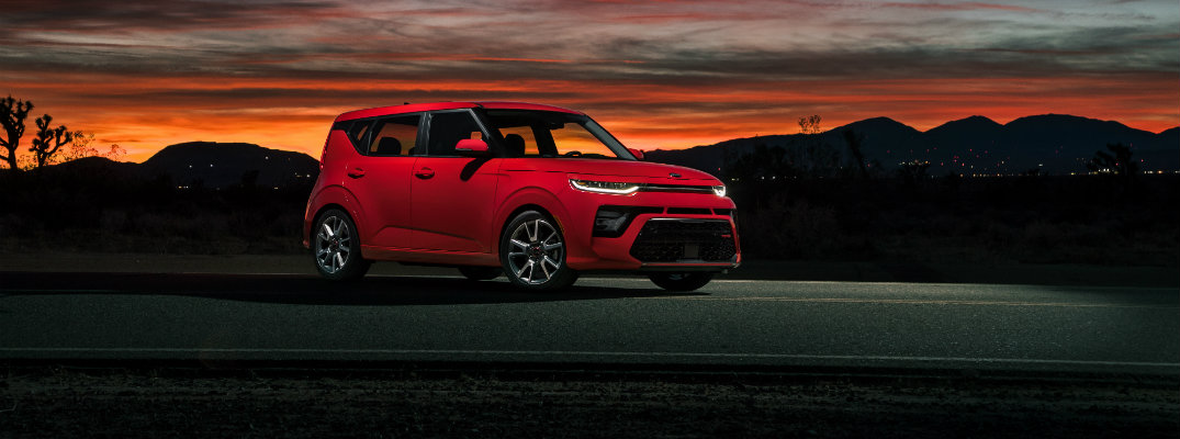 2020 Kia Soul GT-Line exterior shot with red paint color parked on an empty highway track at a night sunset with a quiet, litup southern town behind it