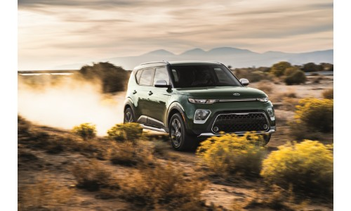 2020 Kia Soul X-Line exterior shot with dark green paint color driving through a dessert off-road terrain while kicking up dust