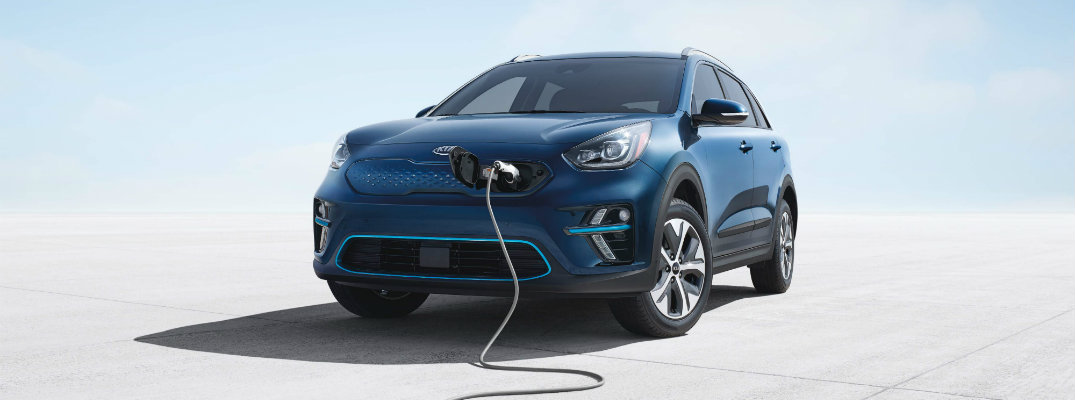 2019 Kia Niro EV exterior shot with blue paint color parked on a concrete lot while it's plugged in and charging