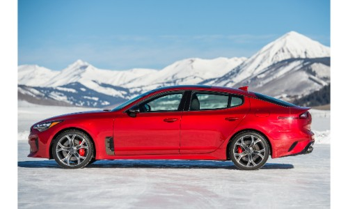 2019 Kia Stinger exterior side shot with red paint color parked in a snowy, icy tundra