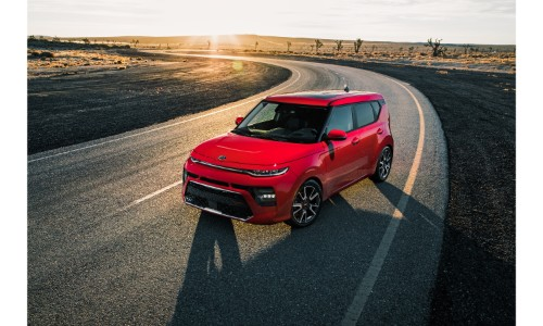 2020 Kia Soul GT-Line exterior shot with red paint color parked on a curving country desert road at sunset