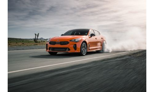 2019 Kia Stinger GTS special edition exterior shot with orange paint color kicking up dust as it speeds down a country highway