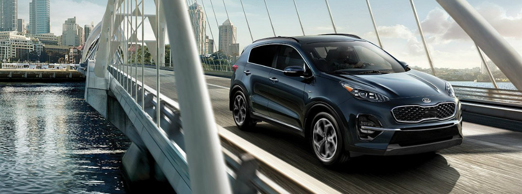 2020 Kia Sportage with gray blue paint color exterior shot driving over water on a bridge as it exits a city