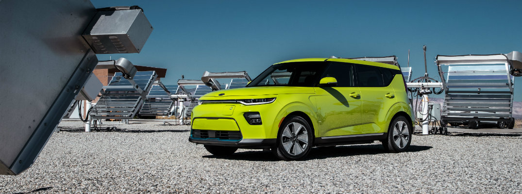 2020 Kia Soul EV exterior shot with lime green yellow paint color parked on a gravel flat plain surrounded by solar panels
