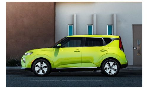 2020 Kia Soul EV exterior side shot with yellow green paint color parked outside of a beige brown building