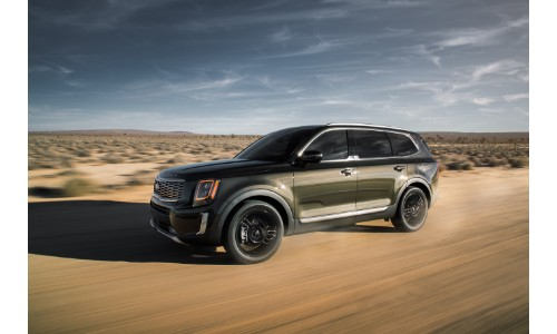 2020 Kia Telluride exterior side shot driving through a barren desert landscape