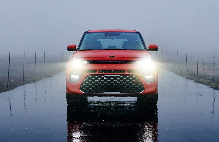 2020 Kia Soul red front view on a rain-slicked road