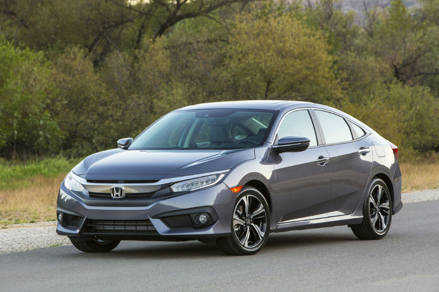2018 honda civic sedan driving on road in front of woods
