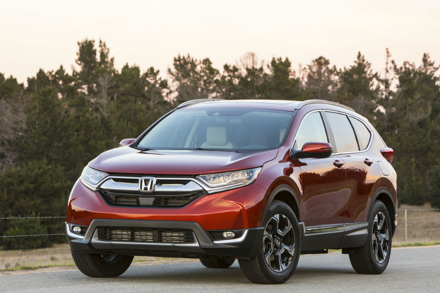 red 2018 honda cr-v parked in front of forest road