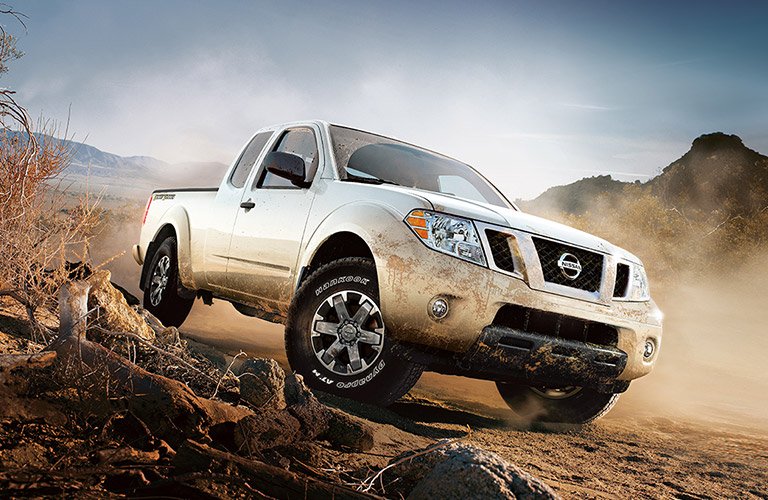 2018 nissan frontier in white climbing over rocks