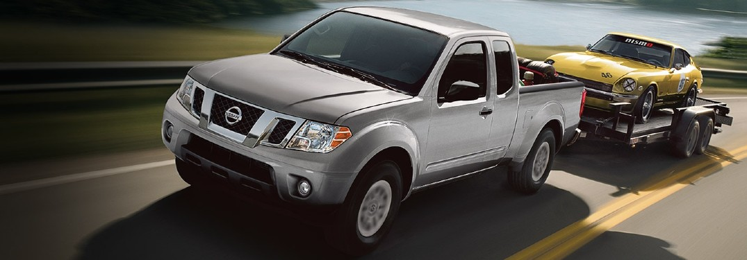 2021 Nissan Frontier towing a trailer with a car on it