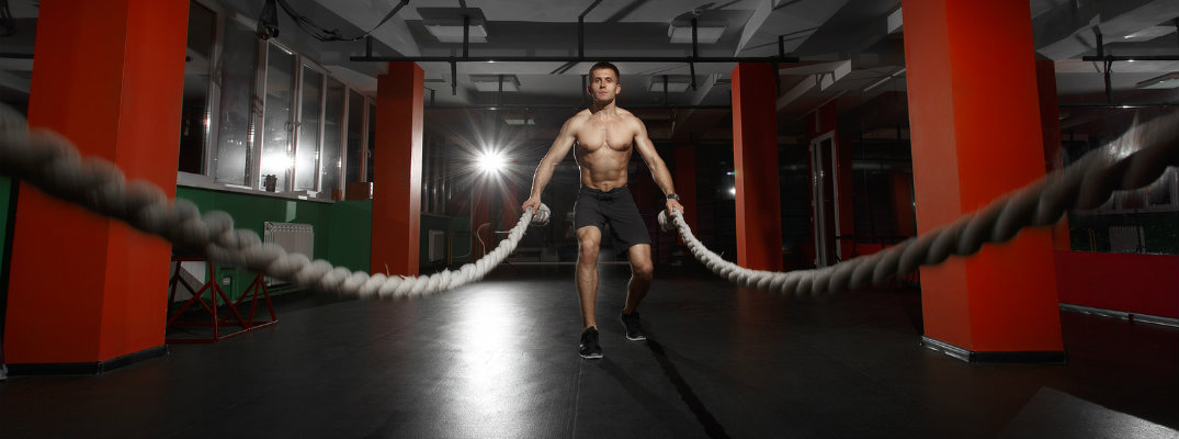 Man in gym working out using battle ropes