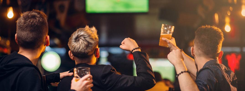 Three men watching sports in a bar