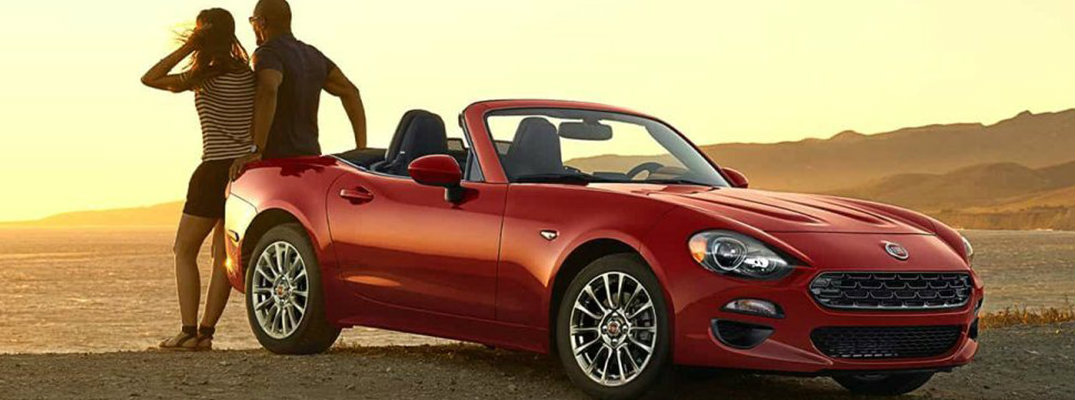 Two people sitting on trunk of 2018 Fiat 124 Spider