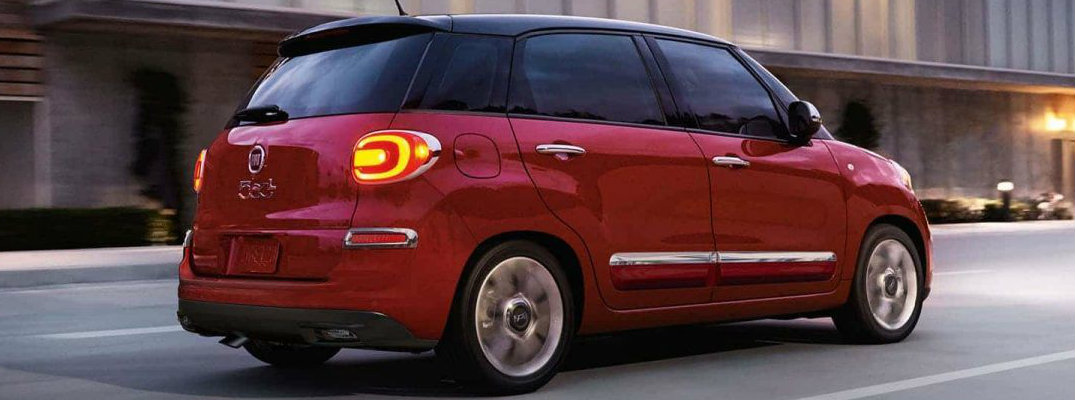 Profile view of red 2018 Fiat 500L driving down city road