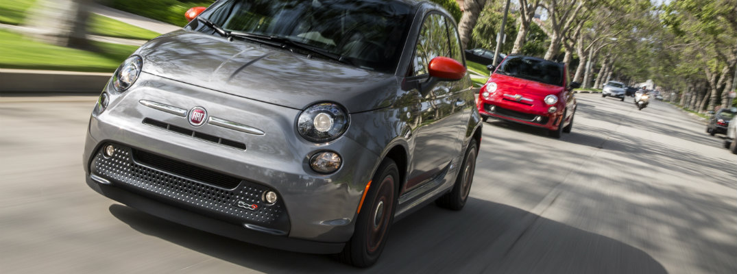 Gray 2018 Fiat 500e driving on lit road with red Fiat model trailing