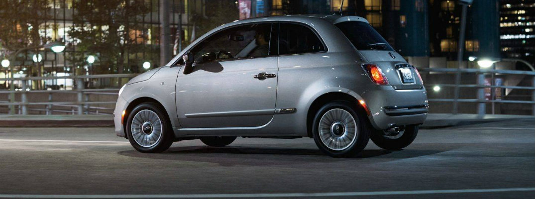 Profile view of silver Fiat 500 driving at night