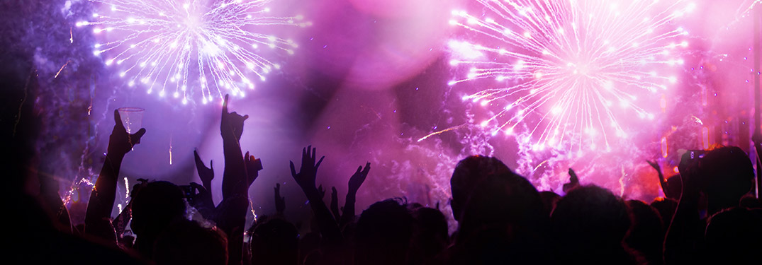 A party outdoors with people celebrating and fireworks purple background