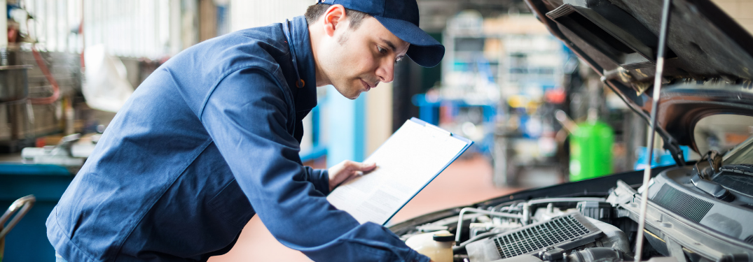 mechanic looking at engine of car under the hood while holding clipboard