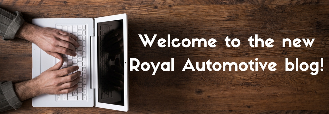 Man sitting at a wooden table typing on a white lap top next to text reading welcome to the new Royal Automotive Blog