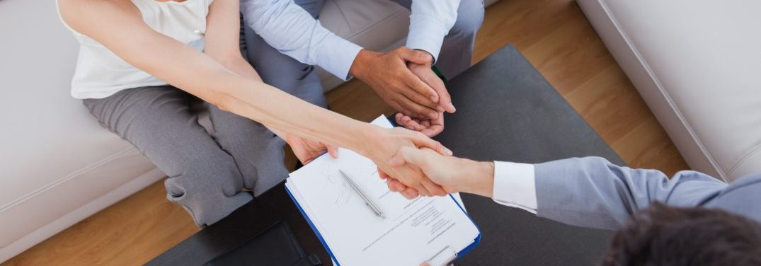 People shaking hands after filling out paperwork that is on a table
