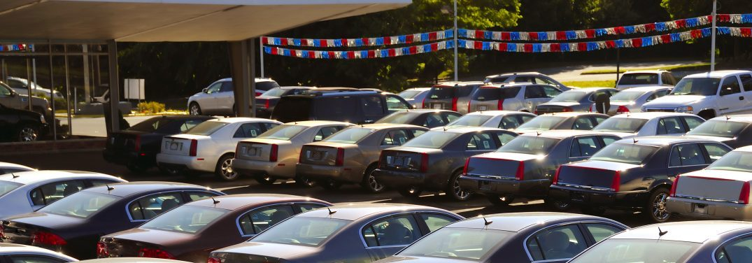 A row of cars parked at a car dealership with a banner overhead