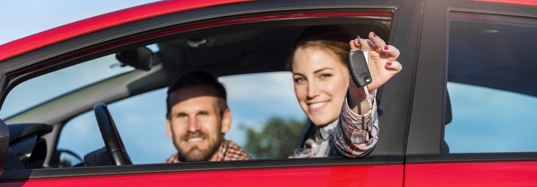 Woman and man sitting in a red car with the woman sitting in the driver seat holding out the keys