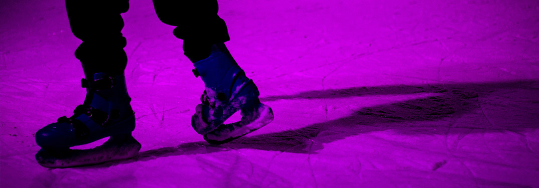 Close-up view of a person ice skating around a purple light