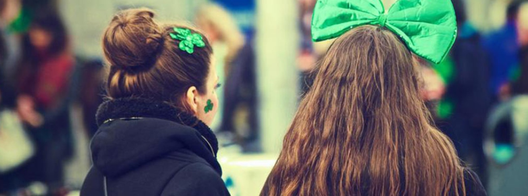 Image of two women watching a St. Patrick's Day parade