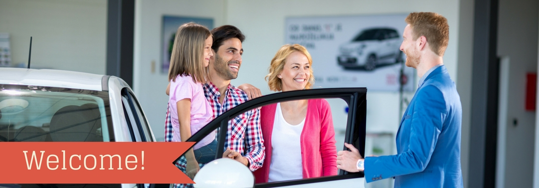 A sales person talking to a family next to a car