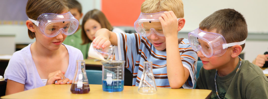 Kids wearing safety goggles and conducting chemistry experiments