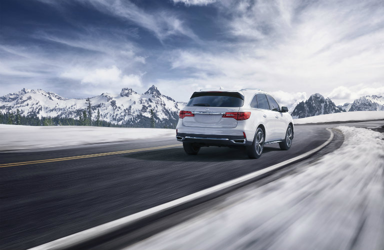 2018 Acura MDX in white driving down an empty road in winter