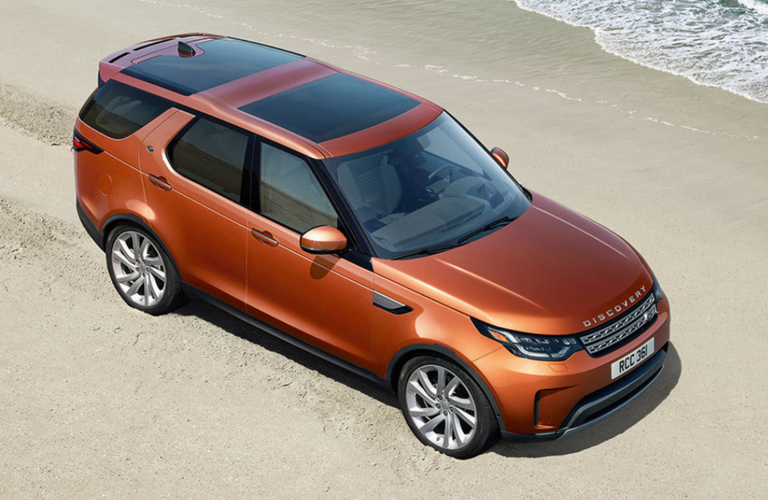 2018 Land Rover Discovery in orange parked on a sandy beach