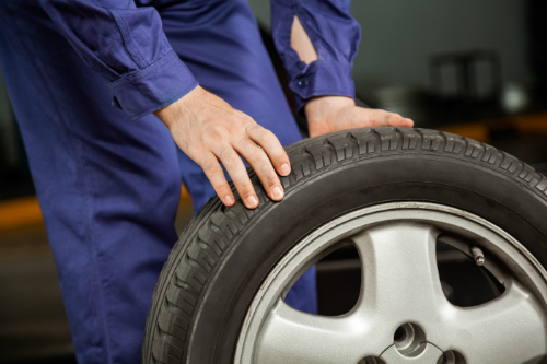 Mechanic in a blue jumpsuit rolling a tire