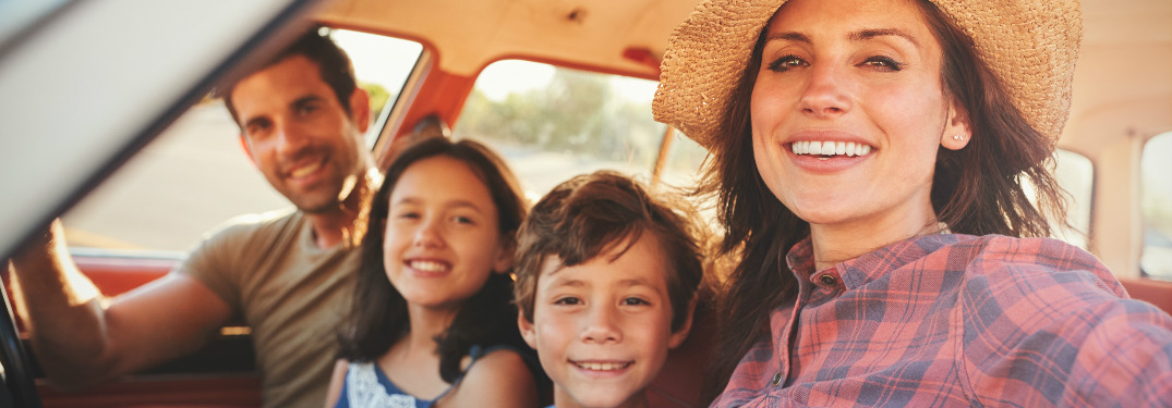 Family of four sitting in the front of their vehicle