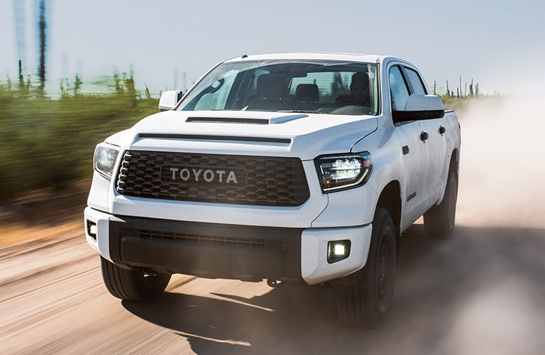 2019 Toyota Tundra in white driving on a dusty road