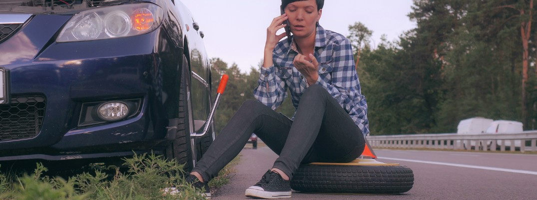 Young woman sitting on flat tire on the side of the road