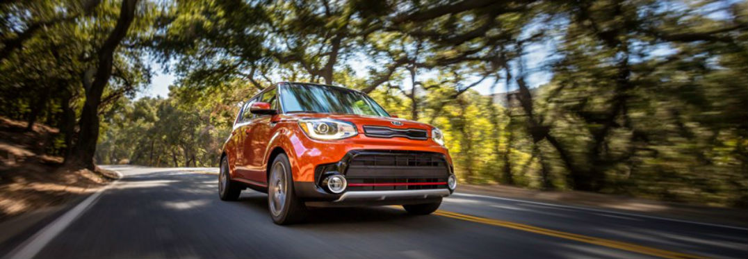 2018 Kia Soul Awarded Prestigious Accolades with image of a Kia Soul in orange driving past trees