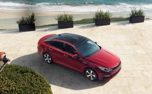 aerial view of red kia optima by beach