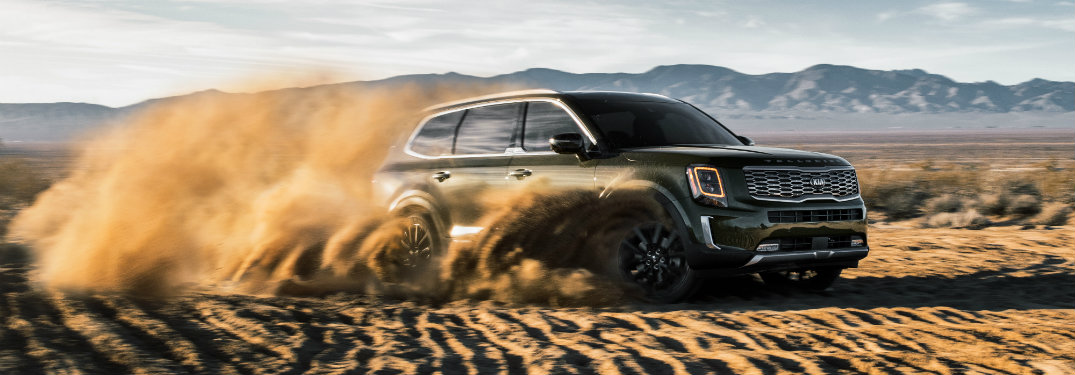 black kia telluride driving through dirt and dust