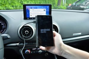 person holding plugged in android phone in car
