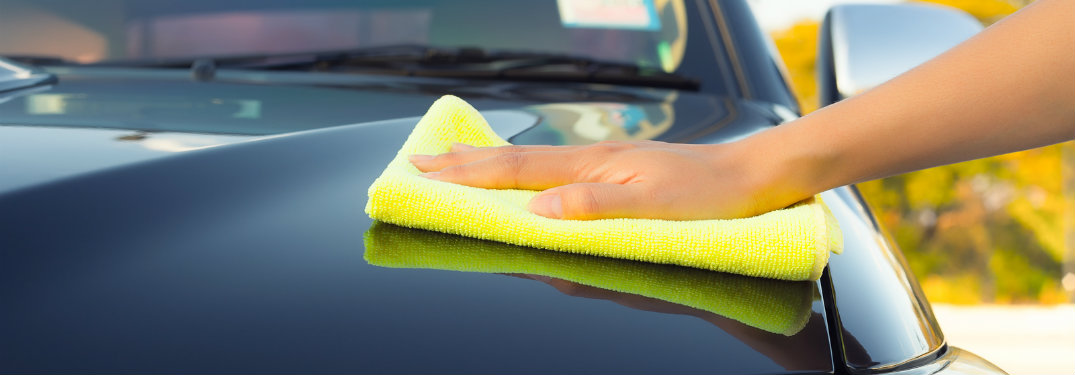 person wiping hood of car with yellow towel