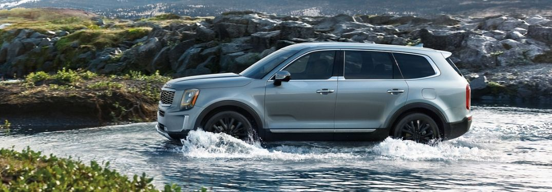 2020 Kia Telluride from exterior driver side driving through water with mountain in background
