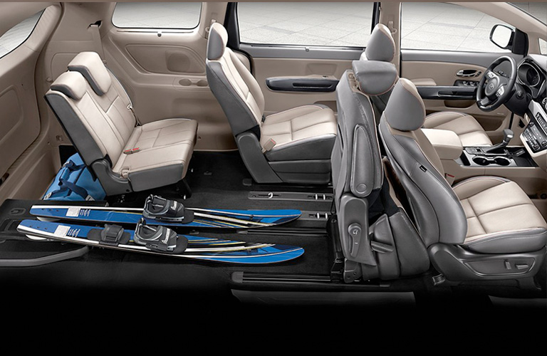 Interior of 2020 Kia Sedona showing three rows of seating and skis