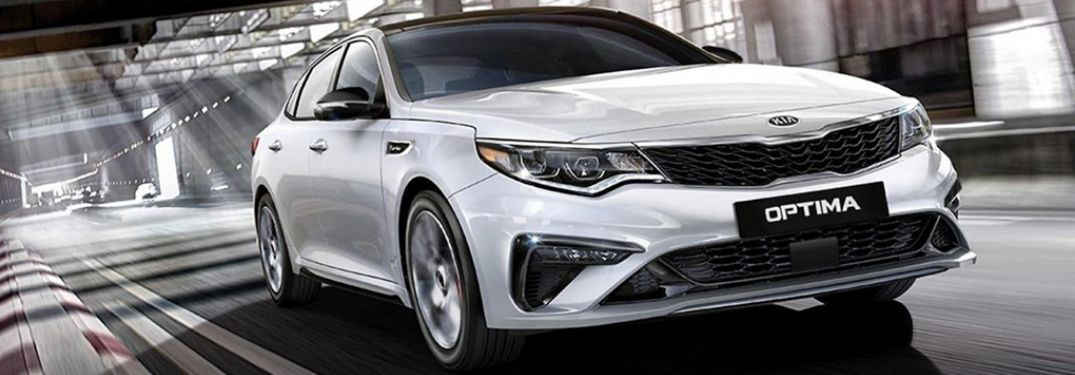 White 2020 Kia Optima on road from exterior front passenger view