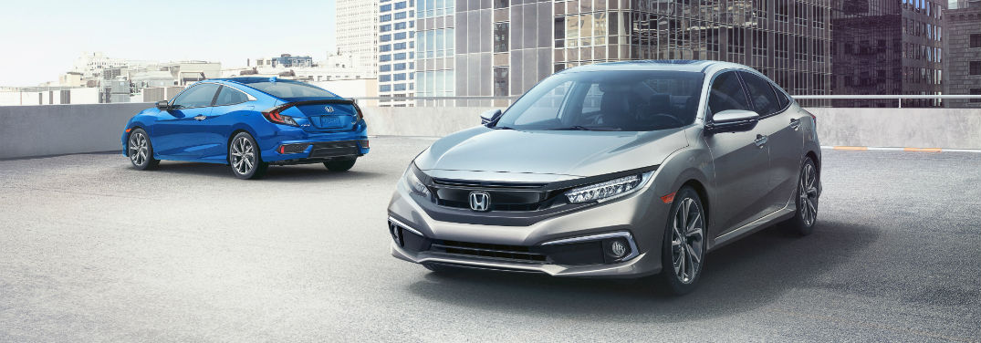2019 Honda Civic Sedan and Coupe New Athletic Design with an image of 2019 Honda Civic Sedan and 2019 Honda Civic Coupe parked on the roof of a parking garage in a city