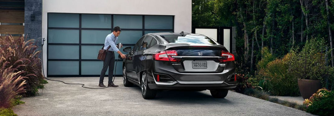 What is a Plug-in Hybrid? with image of a man charging his 2018 Honda Clarity Plug-in Hybrid in a driveway