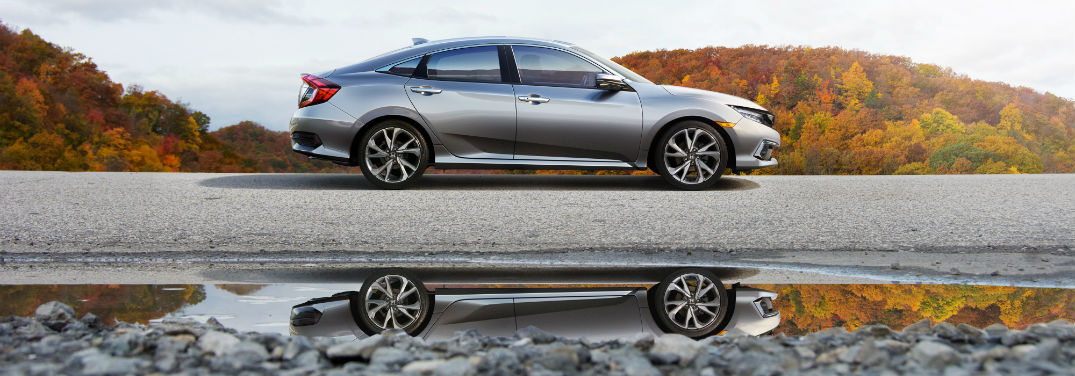 2019 Honda Civic Sedan Pricing and Features with image of a 2019 Honda Civic Sedan parked with reflection showing in a puddle and colorful trees in the background